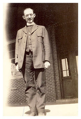 Image of Fr. Henry Hogebach standing in front of St. Joseph's Indian School.