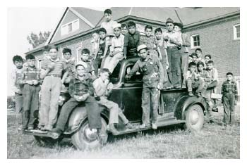 A large group of Native American boys posing for a picture on a pick-up truck.