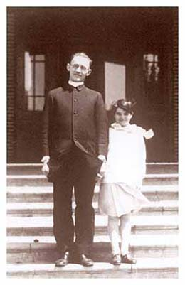 Image of Fr. Henry and a Native American child standing on the front steps of the St. Joseph's Indian School building.