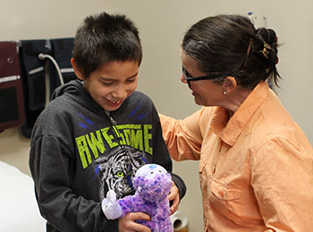 A health care staff is taking special care to meet the health care needs of a male Native American student.