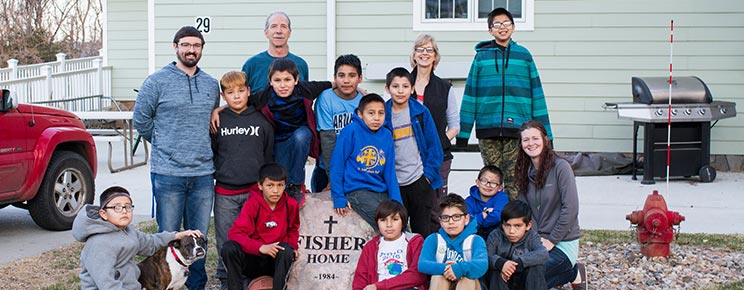 Students and staff stand outside the Fisher Home, one of the 21 homes in St. Joseph's Residential Living program.