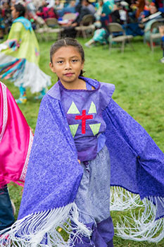 A young Native American girl wears purple regalia at St. Joseph's powwow. According to powwow etiquette, one should ask permission before touching any part of a dancer's regalia.