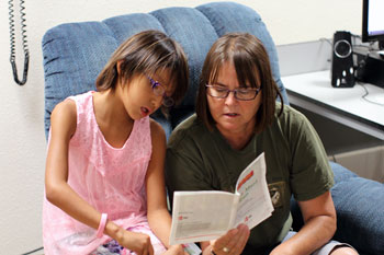 St. Joseph's Indian School staff reading a book to a Lakota girl