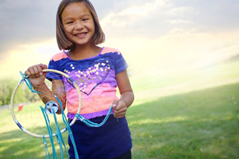 Lakota girl holding a colorful dreamcatcher.