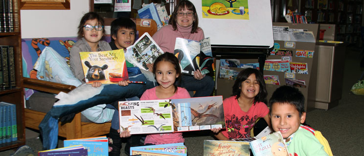 Native american youth reading books donated by generous people like you.