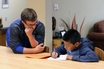 St. Joseph's staff member helping a Lakota boy with his homework.