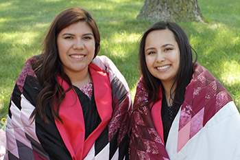 Two young Native American women have a star quilt draped around their shoulders.