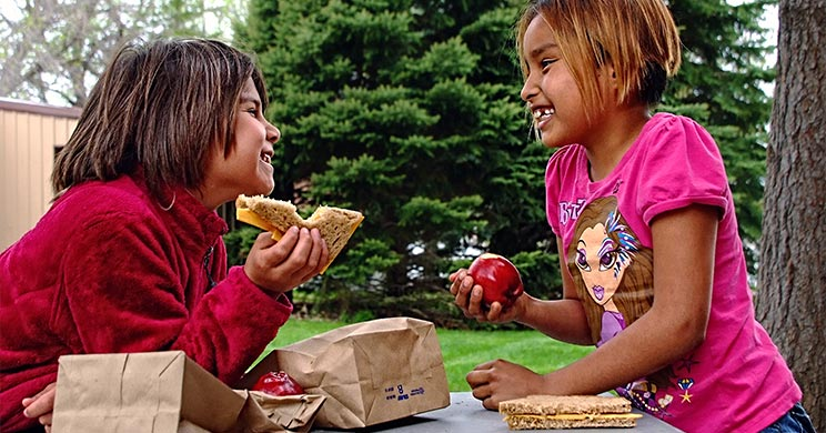 Two Native American girls eating a sandwitch and apple.